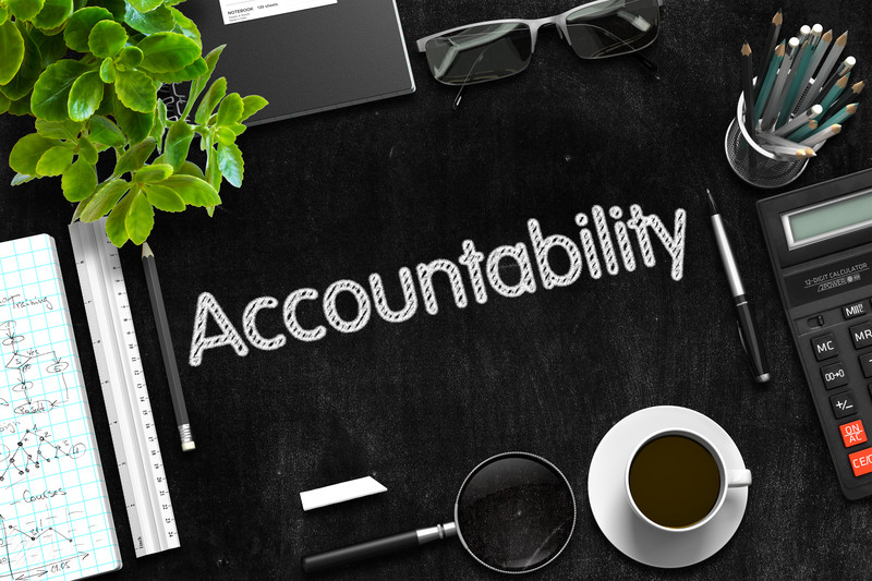 "Photo of a desktop with the words ""Accountability"", a magnifying glass and a cup of coffee"