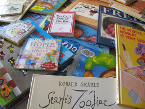 Assorted books on a table, mostly children's books.